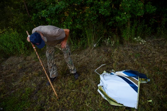 Dan Plas looks at a piece of debris from a small plane that crashed into a home in Hope Mills, N.C., late Thursday evening on Friday, June 28, 2019.