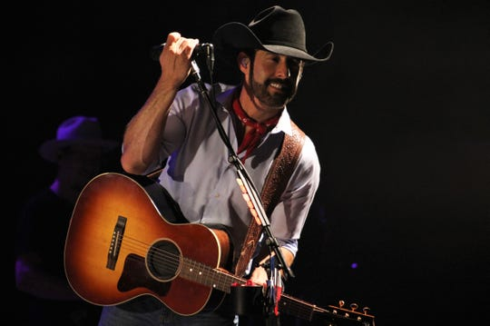 Country singer Aaron Watson, sporting a beard, leans away from the mic to give fans a cellphone photo op during his show Friday evening at the H-E-B Pavilion at the Taylor County Expo Center. He later told female fans not to ask him for hat, which he said was given to him by champion rodeoer Tuff Hedeman.