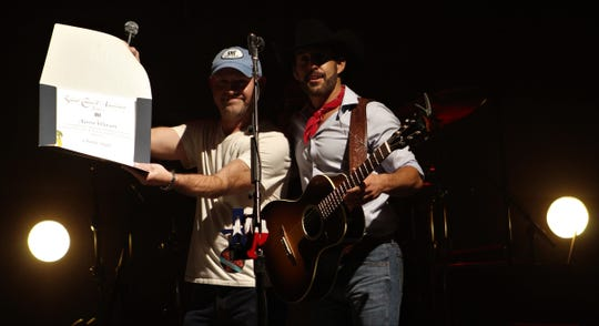 """Mitch Ballard, a Texas-based representative of BMI, shows off an award to country singer Aaron Watson, who achieved 1 million plays of his biggest hit, """"Outta Style"""" at Friday evening's outdoor concert at the Taylor County Expo Center."""