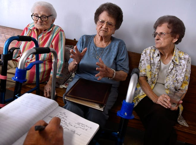 Audean Wheeler (left), Betty Mclure, and Melba Joyce recall stories as Lonnie Wright records them in a notebook June 22. About 60 people gathered for the Shep Homecoming, some of whom were students in the school before it closed in 1948.