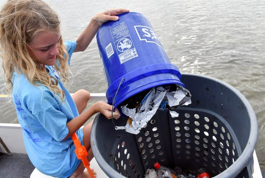 Lucy Mills empties a bucket of trash for a volunteer during Saturday's trash pickup along the Indian River. Dozens of volunteers headed out to the spoil islands in the Indian River near Parrish Park in Titusville to collect trash  during the Keep Brevard Beautiful's Summer Series cleanup.