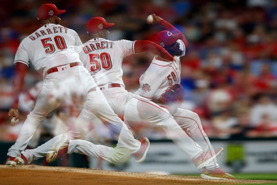 (in-camera multiple exposure) Cincinnati Reds relief pitcher Amir Garrett (50) delivers a pitch in the eighth inning of the MLB National League game between the Cincinnati Reds and the Chicago Cubs at Great American Ball Park in downtown Cincinnati on Friday, June 28, 2019. The Reds won the first game of the three-game series, 6-3.