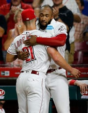 Cincinnati Reds relief pitcher Michael Lorenzen (21) gets a hug from relief pitcher Amir Garrett (50) after pitching out of a jam in the eighth inning of the MLB National League game between the Cincinnati Reds and the Chicago Cubs at Great American Ball Park in downtown Cincinnati on Friday, June 28, 2019. The Reds won the first game of the three-game series, 6-3.