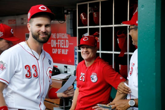 Cincinnati Reds manager David Bell (25) laughs as Cincinnati Reds left fielder Jesse Winker (33) grabs the lineup to give to the umpires before the first inning of the MLB National League game between the Cincinnati Reds and the Chicago Cubs at Great American Ball Park in downtown Cincinnati on Friday, June 28, 2019. The Reds led 2-0 after three innings.