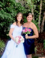 Micalla Rettinger, right, shown with her sister Maria Bohnet during the latter's 2013 wedding. Micalla, known as KK, was her older sister's maid of honor. Rettinger, 25, was killed April 28 by a bullet police do not believe was intended to hit her. No arrests have been made in the case, but a scholarship fund in Rettinger's memory has nearly reached $30,000.