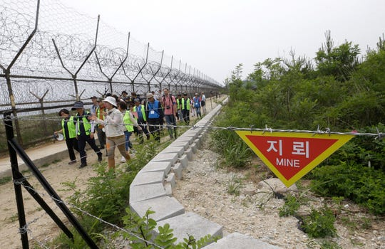 Hikers and journalists walk along the DMZ Peace Trail in the demilitarized zone in Goseong, South Korea.