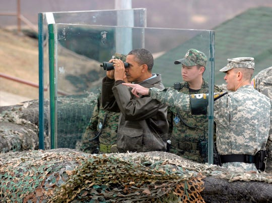 Then U.S. President Barack Obama, second left, looks through binoculars to see North Korea from Observation Post Ouellette in the Demilitarized Zone, the tense military border between the two Koreas, in Panmunjom, South Korea on March 25, 2012.