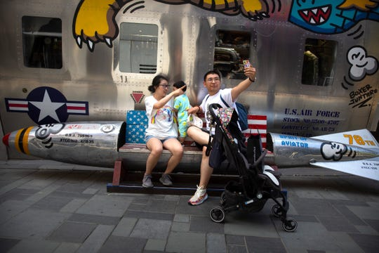 A family poses for a selfie while sitting on a bench shaped like a missile painted with the U.S. flag outside of a clothing store at a shopping mall in Beijing, Saturday, June 29, 2019.