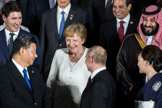 Germany's Chancellor Angela Merkel, center, speaks to China's President Xi Jinping, left, and Russia's President Vladimir Putin, second right, during a family photo session.