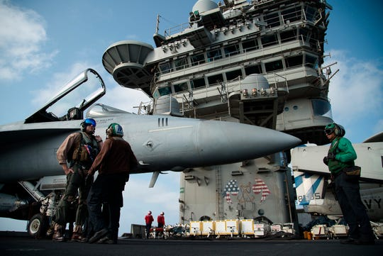 In this June 3, 2019 file photo, a pilot speaks to a crew member by an F/A-18 fighter jet on the deck of the USS Abraham Lincoln aircraft carrier in the Arabian Sea.