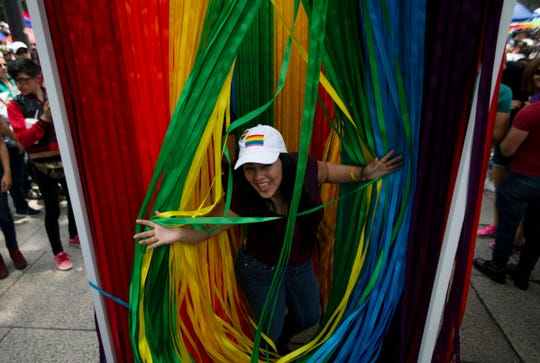 A reveler poses for a photo behind a closet with a curtain made with the colors of the rainbow during the gay pride parade in Mexico City, Mexico, Saturday, June 29, 2019.