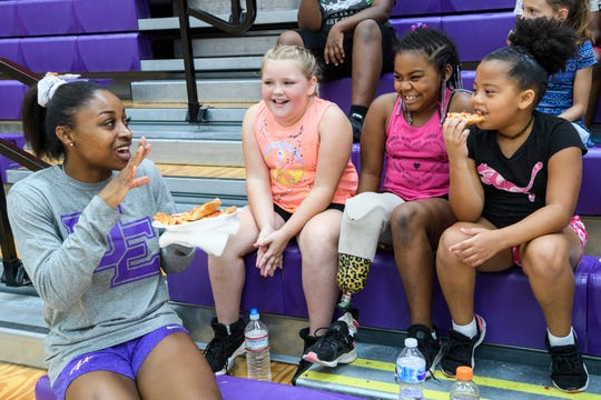 University of Evansville's Lola Bracy, from left, chats with Bentlee Erickson, Damiah Bradley and Kaleyah Harvell as they eat pizza and relax at the end of the Walter McCarty Leadership Academy basketball camp held at UE's Carson Center in Evansville, Ind., Friday, June 28, 2019.