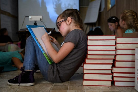 Eight-year-old Lilitth Elsa draws a Harry Potter themed picture as she leans on a stack of dictionaries during the Southside Stars afternoon program in Evansville's Tepe Park neighborhood, Thursday, June 27, 2019. The program received $40,000 from the Don Mattingly Foundation to further develop their youth programing.