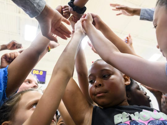 Children from the Boys & Girls Club of Evansville, Dream Center and the YMCA huddle together to say a cheer at the end of the Walter McCarty Leadership Academy basketball camp held at UE's Carson Center in Evansville, Ind., Friday, June 28, 2019.