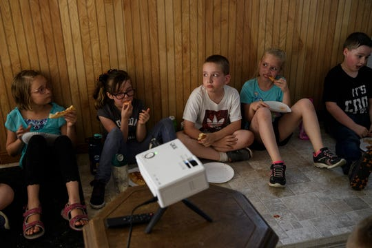 "Members of the Southside Stars afternoon program eat pizza and watch the ""Harry Potter and the Prisoner of Azkaban"" movie in their makeshift trailer in Evansville's Tepe Park neighborhood, Thursday, June 27, 2019.