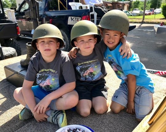 Seven-year-olds Kingston and Karston Keller and Kaenon Brodock, 4, wear Army helmets from their grandpa in the VFW Post 4047 float in the parade at the Fort Benton Summer Celebration on Saturday. The fun continues Sunday.