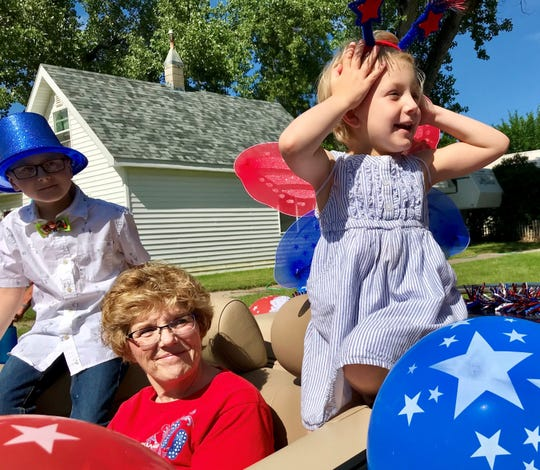 Five-year-old Scarlett Wright (right) and her nine-year-old brother Lawson (in blue hat) spot Minnie and Mickey Mouse at the Fort Benton Summer Celebration.