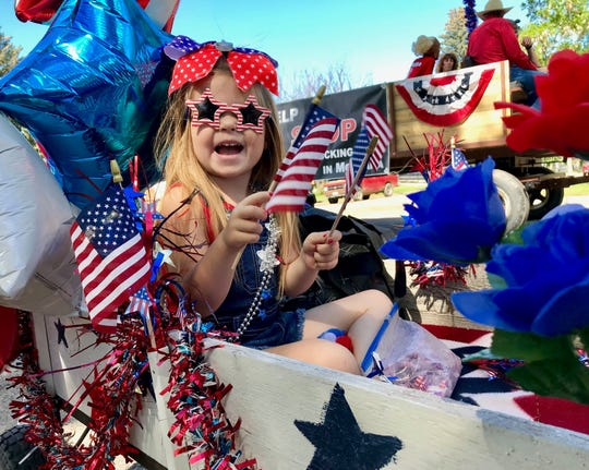 Addyson Ayers, 3, rides in a cart pulled by pony Marylegs (with pig Penny trotting along beside) in the parade during the Fort Benton Summer Celebration.