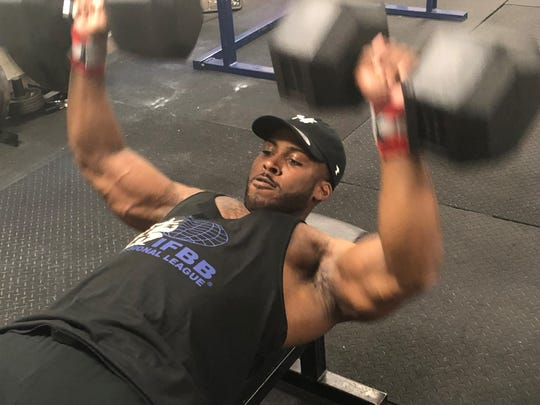 Professional bodybuilder Benquil Marigny works out with dumbbells during a June 17 training session at the John F. Kennedy Center in Henderson.