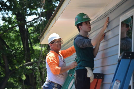 Mike Maddux, UT alum from the class of 1983 (left), and Cody Levi, a sophomore studying psychology and neuroscience (right), install siding on the side of a house in Knoxville on Saturday.