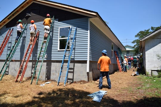 Volunteers divided and conquered the work of installing siding for a house during the Volunteering with the Vols event in Knoxville.