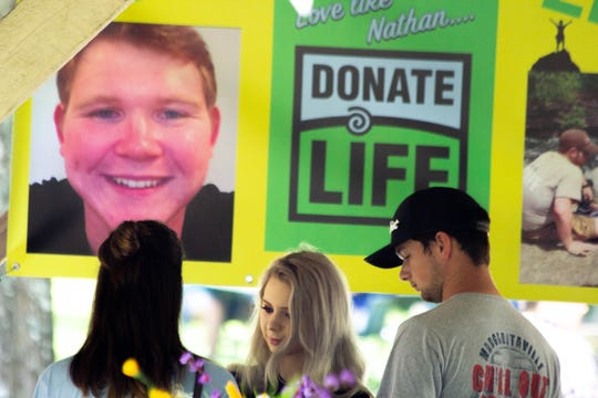 "A photo of Nathan Davis and ""Donate Life"" are seen on a banner during a celebration of life for Davis at Big Ridge State Park on Saturday."