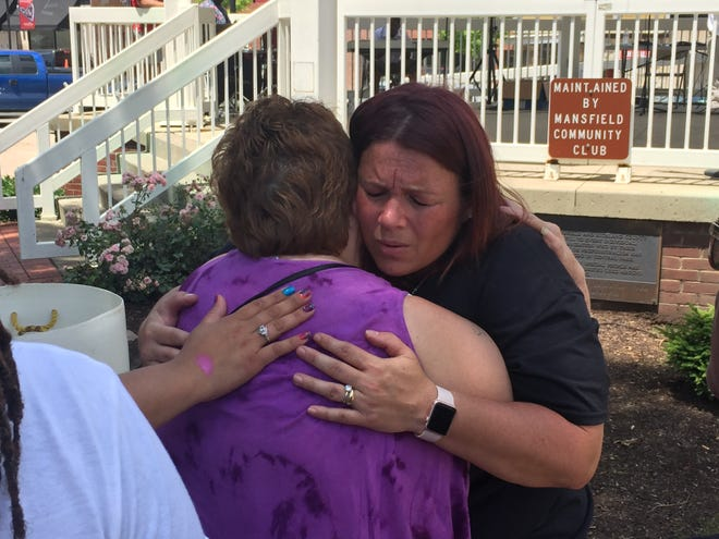 """Amanda Nichols (r) hugs Paula Murray after praying at Saturday's """"Unity in the Community"""" celebration in downtown Mansfield."""