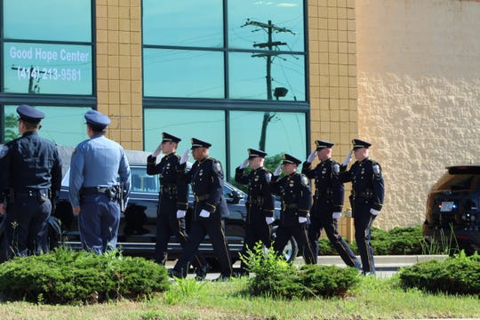 Officers salute the casket carrying the remains of Milwaukee Police Officer Kou Her on June 29, 2019. Her was killed June 18, 2019, when his vehicle was struck by a suspected drunken driver.