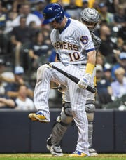 The Brewers' Yasmani Grandal breaks his bat over his knee after striking out in the eighth inning.