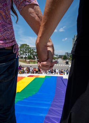 Marchers gather around a giant rainbow flag on the steps of the state capitol building during the Montgomery Pride March and Rally in downtown Montgomery, Ala., on Saturday June 29 , 2019.
