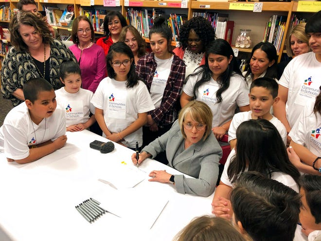 In this April 3, 2019 file photo, New Mexico Gov. Michelle Lujan Grisham signs legislation to raise teacher salaries and increase annual spending on public schools by almost a half-billion dollars at Salazar Elementary School in Santa Fe, N.M.