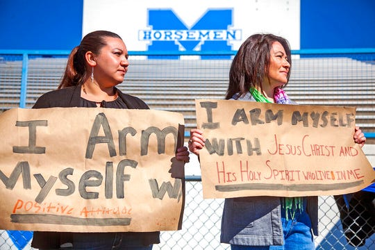 In this March 14, 2019 file photo, Gladys Rimkus and Annette Legits, staff members at St. Michael's High School, hold up signs during a demonstration with students and faculty against gun violence in schools in Santa Fe.