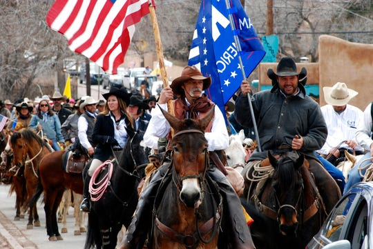 Un this March 12, 2019 file photo, advocates for gun rights in New Mexico including rural ranchers joined with a interstate group called Cowboys for Trump, approach the New Mexico state Capitol in Santa Fe on horseback.