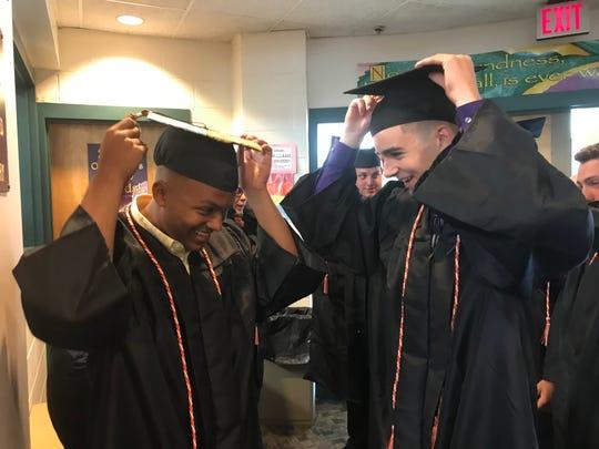 Dover High School graduates Hunter Salerno, left, and Matthew Holder adjust their caps prior to graduation on Saturday, June 29, 2010.