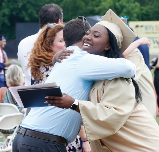 Geneva Brown gives social studies teacher Lance Mill a hug during the Beacon High School graduation ceremony at Dutchess Stadium in Fishkill on June 29, 2019.
