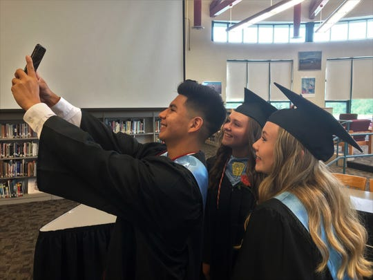 Dover High School graduates, from left, Sergio Alexis Ramirez Recinos, Brooke Leary and Amber Bosser pose for a selfie shortly before graduation on Saturday, June 29, 2019.