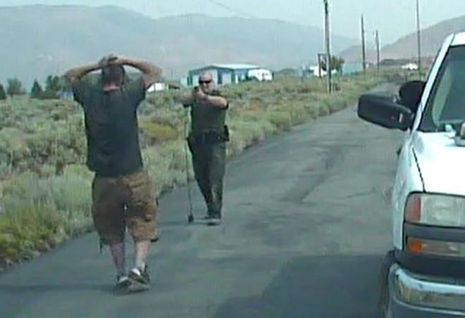 A photo showing Washoe County Sheriff's Deputy Yancy Butler pointing a gun at suspect Cory Stephens as he walked backward to Butler's patrol vehicle on Aug. 4, 2017.