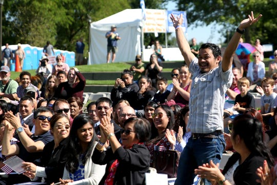 Yan Ardianto celebrates as his home country of Indonesia is called during the first naturalization ceremony held at the World Beat Festival at Riverfront Park in Salem on June 29, 2019. Hundreds attended the ceremony where 59 people from 26 countries were sworn in as U.S. citizens.