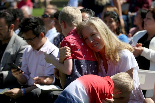 Krista Anderson, originally from the United Kingdom, hugs her sons Kaiden, 7, and Logan, 4, after she became a U.S. citizen during the first naturalization ceremony held at the World Beat Festival at Riverfront Park in Salem on June 29, 2019. Hundreds attended the ceremony where 59 people from 26 countries were sworn in as U.S. citizens.