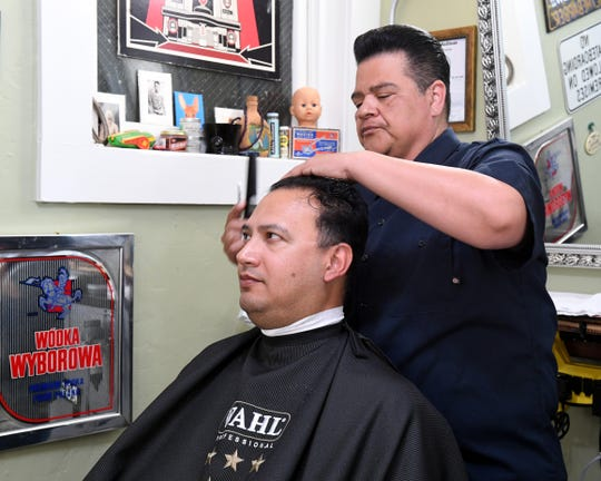 Barber CJ Hernandez cuts a client's hair. June 22, 2019.