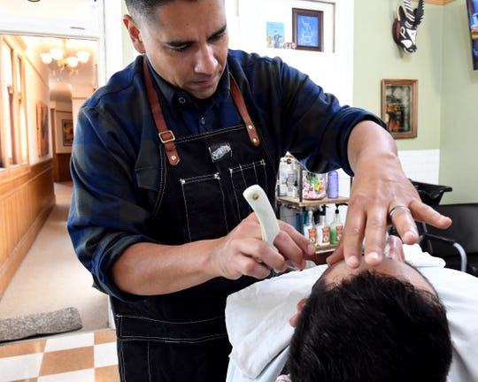 Barber R.G. at Furey's Old Town Barber shaves a client with a straight razor. June 22, 2019.