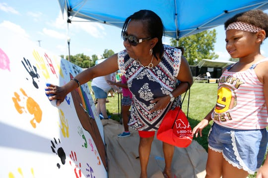 Marcella Donson places her handprint on a painting which featured a clenched fist with Pride colors on display at the Greene County Democratic Progressive Caucus booth during the Juneteenth Celebration at Silver Springs Park on Saturday, June 29, 2019 in Springfield, Mo.