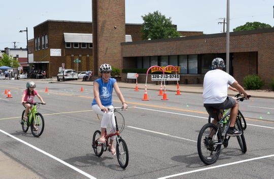Kathy Geislinger rides a bike, Saturday, June 29, 2019 at the East Side Block Party on East Germain St. Geislinger is a program manager with CentraCare Health, and she works with Feeling Good MN and Project Brain Safe to teach bike safety and riding to communities.