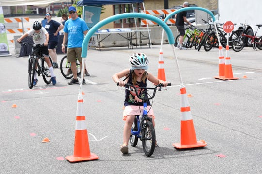 Lucy Kulmaczewski, from Homen, Wis., rides through an obstacle course to teach kids how to safely ride bikes, Saturday, June 29, 2019 at the East Side Block Party on East Germain St.