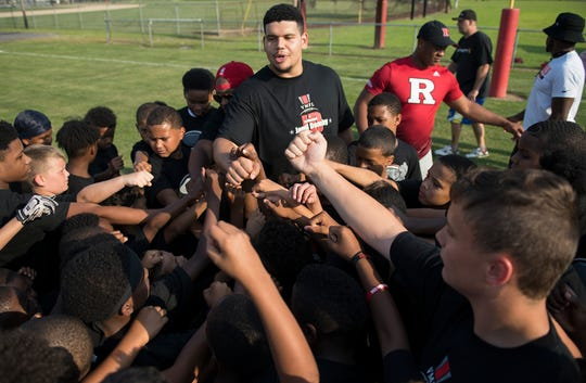 Jamil Demby, a Vineland High School graduate and current Los Angeles Ram, joins in on a huddle as Demby holds a free youth football camp in Vineland on Friday, June 28, 2019.