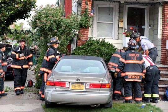 Yonkers firefighters along with Yonkers Police and Empress Ambulance, evaluate the scene after a car crashed into the front of this home at 59 Kimball Avenue in Yonkers, June 29, 2019. Two people were injured in the accident.