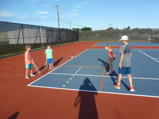 Tennis players Camryn Coppelli (from left to right), Kaden Koetter, Vivian Coppelli and Quinn Coppelli play a game at Hirschi's courts in the Neighborhood Tennis Program earlier this month.