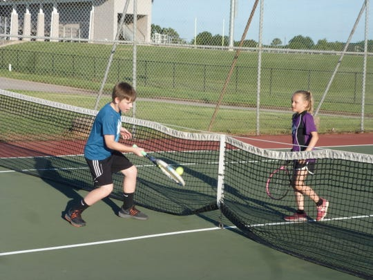 Kolton Scharbrough and Vivian Coppelli play a game in Iowa Park at the Neighborhood Tennis Program.