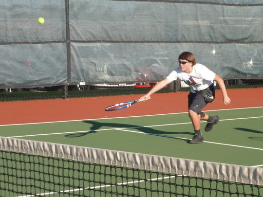 Hayden Lovelady reaches for a  shot at Iowa Park's courts  at the Neighborhood Tennis Program.