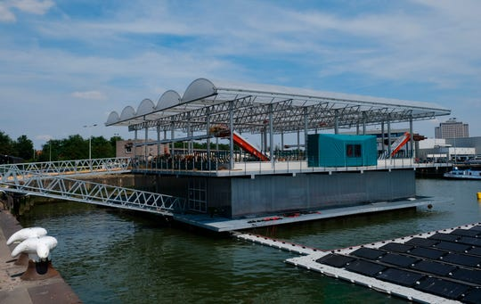 In this photo taken Monday, June 24, 2019, a futuristic three-storey floating farm is moored in Rotterdam harbour, Netherlands, where is is ideally placed to use waste products from a local golf course, brewing company, and a soccer club to claim its green credentials.  The floating dairy farm has one robot that milks the cows, another that automatically scoops up the manure, and a roof designed to collect rain water, trailblazing a way to produce dairy foods within a busy modern city for growing populations, according to the small holding farmer Peter van Wingerden.